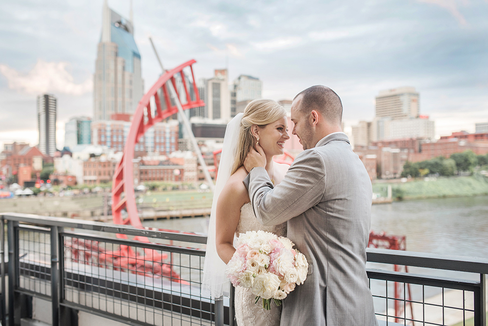 Maddie and Johnny Smiling In Front of the Nashville Skyline at Maddie and Johnny's Wedding at The Bridge Building Event Spaces